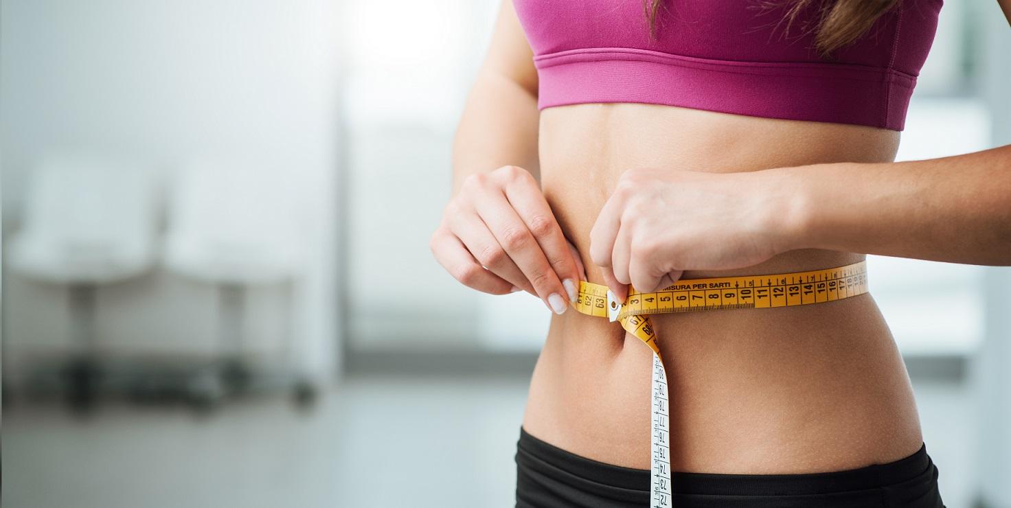 mujer tomándose las medidas de la cintura